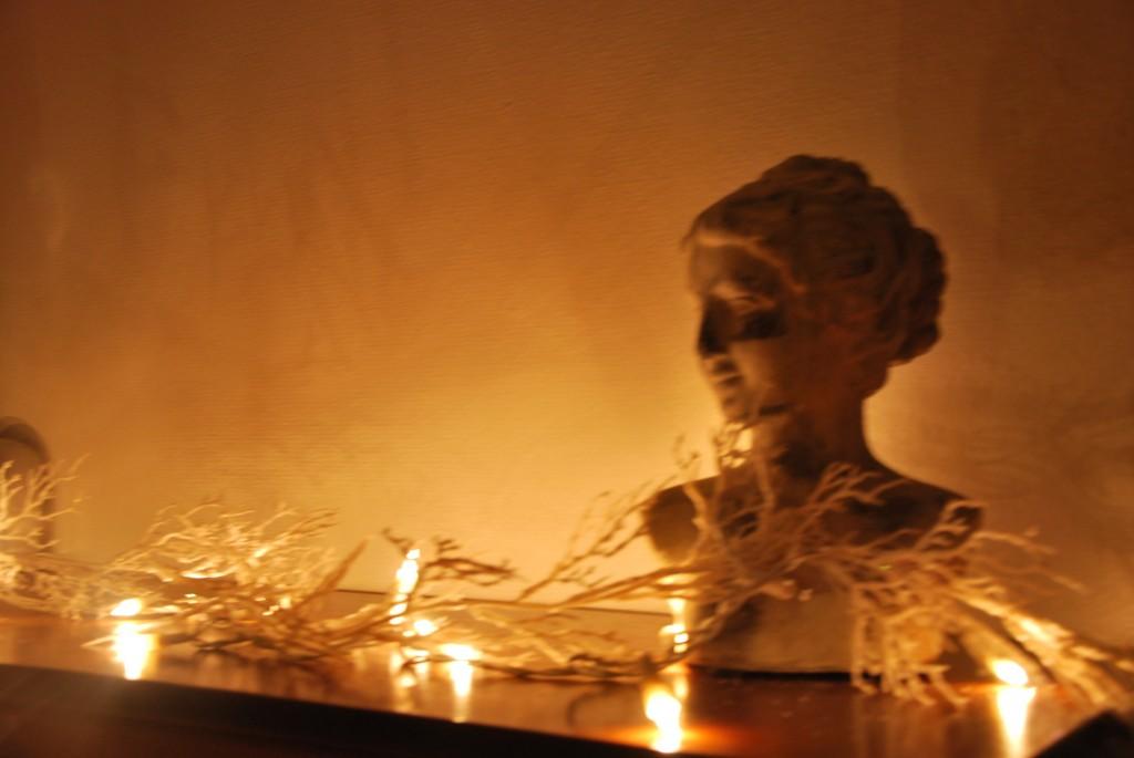 la douce lumière de la guirlande confère une certaine noblesse à ce buste
